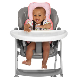 Baby sitting in a high chair with the [Clevamama] ClevaCushion Nursing Pillow & Baby Nest - Not Too Big (Coral)