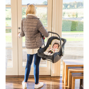 Mother carrying child in a baby basket while child is in the [Clevamama] Grey ClevaCushion Nursing Pillow & Baby Nest - Not Too Big