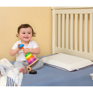 Child playing on the cot bed with the [Clevamama] ClevaFoam Toddler Pillow - Not Too Big