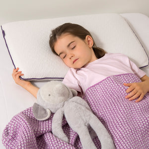 A young girl sleeps in a junior pillow, with purple blanet