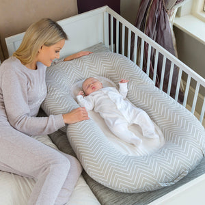 Baby lying in the [Clevamama] Mum2Me Maternity Pillow & Sleep Pod - Not Too Big