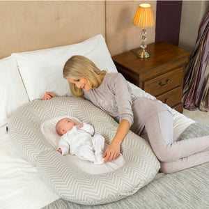 Mother looking at infant lovingly in the [Clevamama] Mum2Me Maternity Pillow & Sleep Pod - Not Too Big