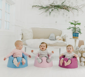 3 little toddlers sit on Bumbo Baby floor sit side by side in the living room