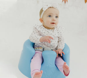 A young toddler sit on Bumbo baby floor seat in powder blue
