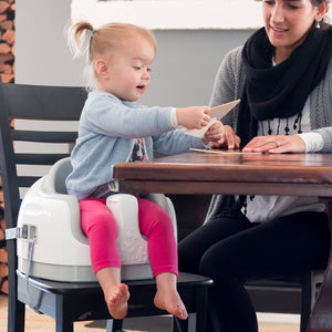 Toddler girl using Bumbo multi seat strapped  as a high chair on dining table