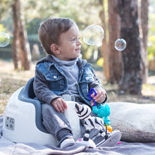 Load image into Gallery viewer, A toddler boy is sitting on Grey Bumbo Multi Seat as a floor chair outdoor
