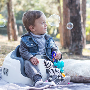 A toddler boy is sitting on Grey Bumbo Multi Seat as a floor chair outdoor