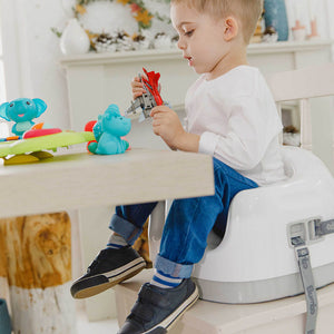 A toddler bow sitting on Bumbo Multi Seat baby chair strapped in dining chair as a high chair, playing toys and Bumbo Suction toys
