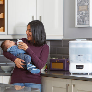 Mother feeding baby after using the [Tommee Tippee] Electric Steriliser & Dryer White - Not Too Big