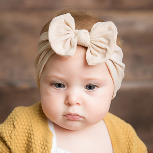 little baby wearing beige headband bow