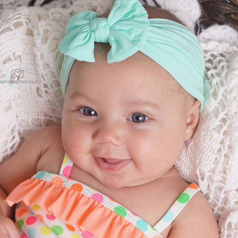 little baby wearing mint green headband bow in bed