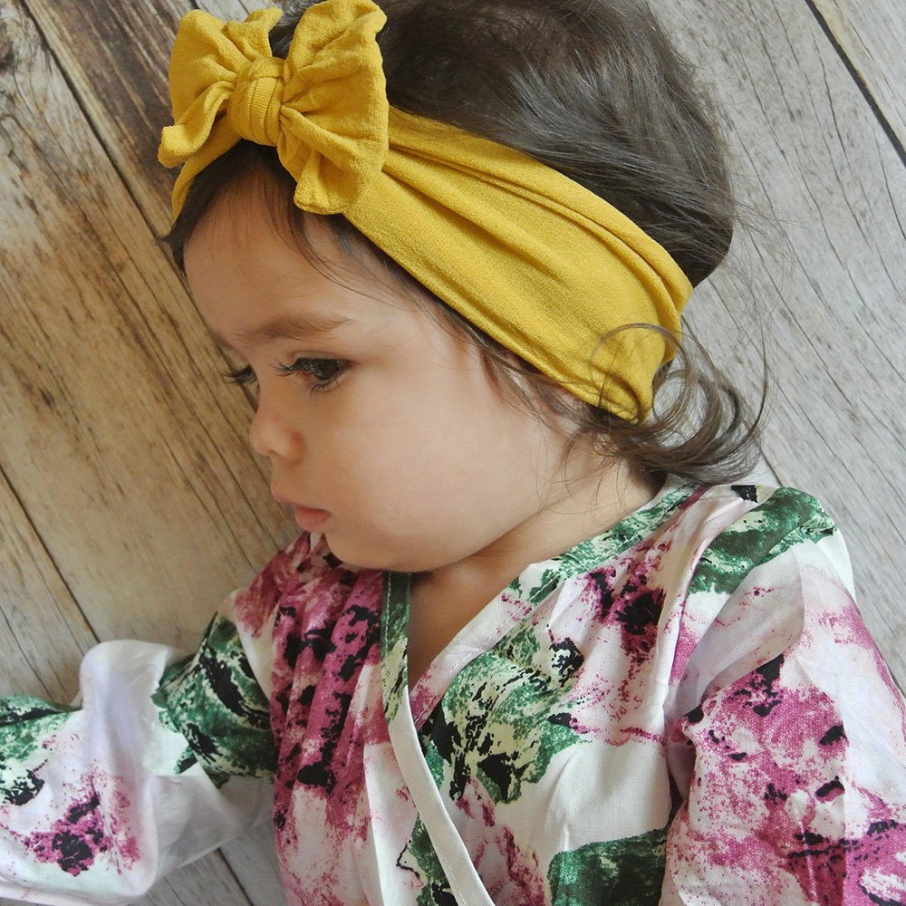girl wearing maize headband bow in flower shirt on wood floor