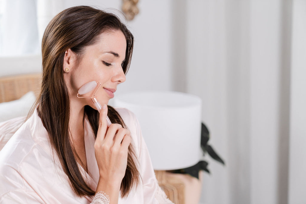 Woman using Nataussie's rose quartz face roller on her beautiful skin