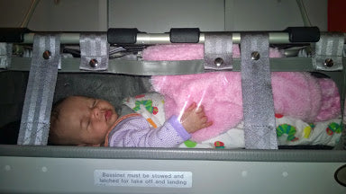 baby asleep in plane bassinet