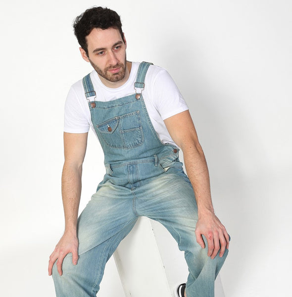 Seated wearing pale wash Uskees denim overalls.