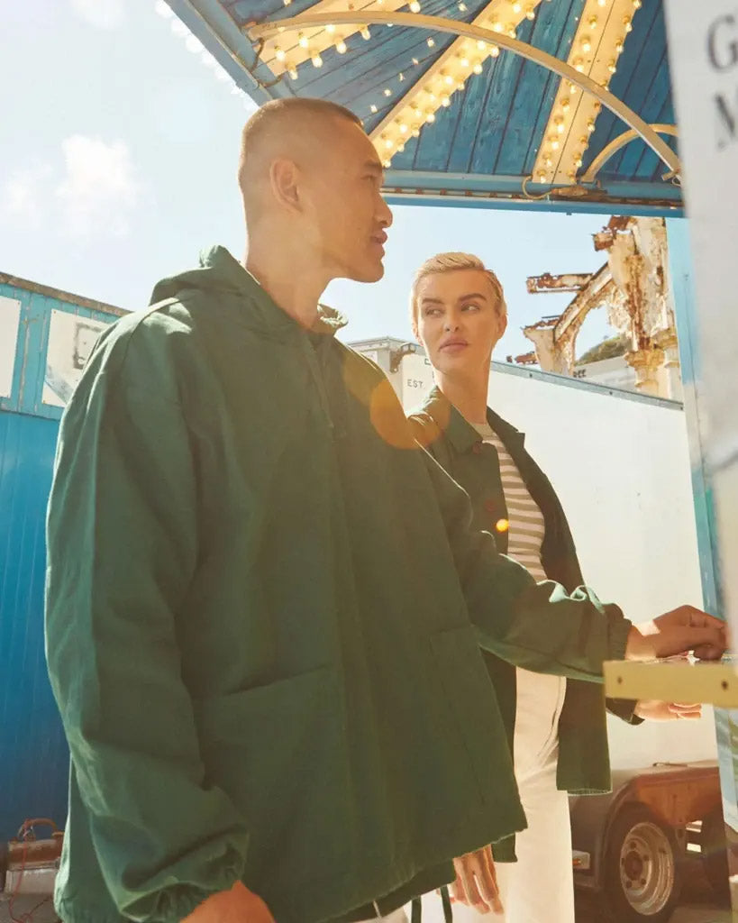 Couple wearing green Uskees tops at seaside snack kiosk.