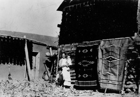 Photo of author's great grandmother with author's father standing in front of handmade woven blankets and chile ristras in Chimayo, circa 1936