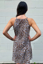 Load image into Gallery viewer, Model is showing the back of the dress and the halter detail that makes the straps.