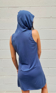 model's back is facing us, and the hood on the dress is pull over her head. The dress is grey and has no sleeves.