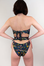 Load image into Gallery viewer, This shows a model wearing a strapless one piece  swimsuit, her back is facing us. There is a fabric band that goes across her mid back. The swimsuit is in a shade of bright red and blue and yellow flowers.