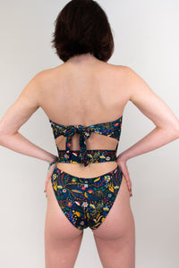 This shows a model wearing a strapless one piece  swimsuit, her back is facing us. There is a fabric band that goes across her mid back. The swimsuit is in a shade of bright red and blue and yellow flowers.