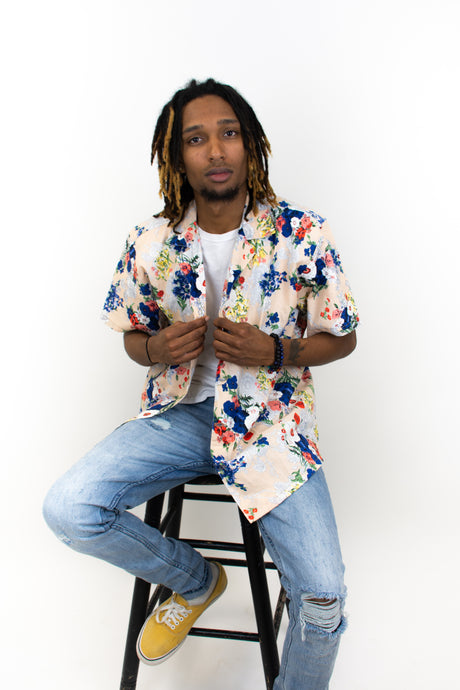 This is a photo of a model wearing a slim cut button up that he is wearing completely opened. It has a tan background and has blue and red painted flowers bursting all over the shirt.