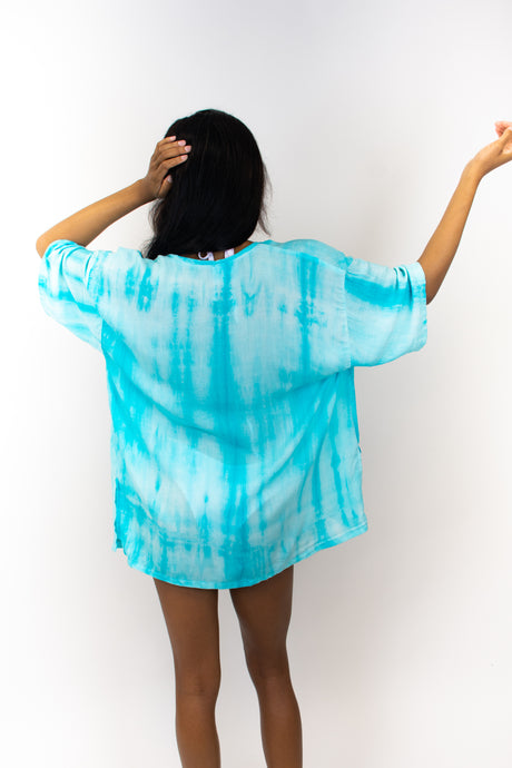 The model in this photo is wearing a blue tie-dyed kimono, the shade of blue is a bright sky blue. The kimono is very flowy and boxy, it reaches below the crotch of the model. The sleeves of this kimono reach just above the elbow.
