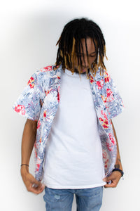 This is a slim cut men's button up shirt that is white with a blue and vibrant fuchsia print on it. The model is wearing it open with a white T-shirt underneath.