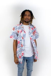 This is a photo of a model wearing a slim cut button up shirt, he is wearing it open and there is a bright fuchsia and sky blue print on it.