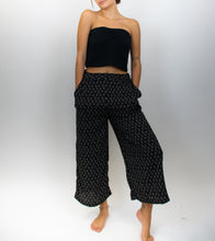 Load image into Gallery viewer, This image shows a model wearing a black top with wide-leg black pants. The pants have a small tan diamond pattern on them, and they hit just above the ankle.