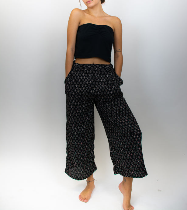 This image shows a model wearing a black top with wide-leg black pants. The pants have a small tan diamond pattern on them, and they hit just above the ankle.