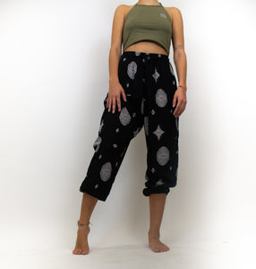 The model in this photo is wearing a pair of black pants that are baggy and singe at the ankles, the pants are black with a red and white diamond pattern on all of the pants. There is a drawstring at the waist of the pants and the pants sit high on the hips.