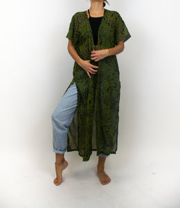A photo of a model wearing an outfit with a long army green kimono that has a black and gold leopard print on it.