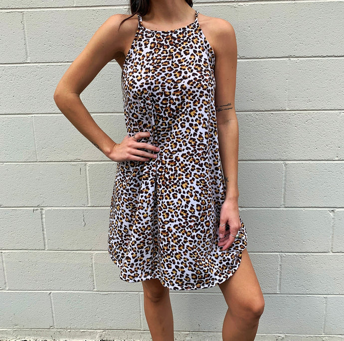 Model is wearing a short cheetah print dress that has halter top traps and hits just above her knee.