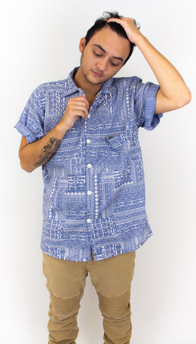 This is a slim fit button up shirt that has white buttons and is jean colored blue with a bandana-like print on it.