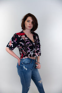 This photo shows a model wearing a pair of jeans and a cropped button up shirt. The shirt is navy with the print of red flowers as well as pink and lilac flowers, there are also light purple butterflies flying around the flowers in the shirt.