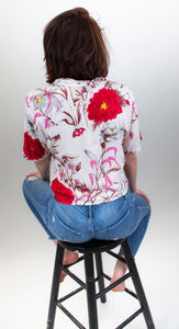 This photo shows a model with her back facing us, she is sitting on a barstool and is wearing jeans and a cropped button up shirt. The shirt has a cream background and big red and pink flowers on it, also accompanied by light purple butterflies.