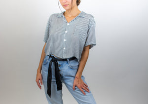 In this photo a model is standing up and wearing the cropped button up shirt, this photo clearly shows the length of the top, it reaches just below the bellybutton.