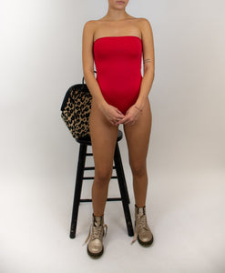 This photo shows a model wearing the same strapless one piece swimsuit, she is facing us. The swimsuit is in the color red.