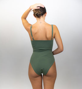 This shows the model wearing the bodysuit and nothing else, her back is facing us.
