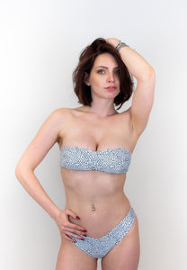 This is a photo of a model wearing the same strapless swimwear top, but it's in the pattern with black dots all over the white suit