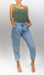 A photo of a model wearing jeans and an army green bodysuit. The bodysuit has spaghetti straps and is tight on the model.