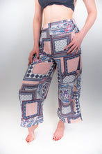 Load image into Gallery viewer, The model in this photo is wearing a pair of pink patterned pants, these pants are very flowy and wide-legged and they sit high on the hips. The print on the pants are almost square looking with blue details, it looks like a patchwork print that is large scale.