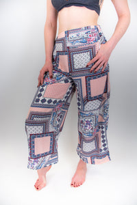 The model in this photo is wearing a pair of pink patterned pants, these pants are very flowy and wide-legged and they sit high on the hips. The print on the pants are almost square looking with blue details, it looks like a patchwork print that is large scale.