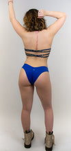 "Load image into Gallery viewer, This photo shows a model wearing the same pair of cheeky swimwear bottoms , this time in the color deep blue. There is a small ""hilo"" logo centered in the back of the bottoms. The models back is facing us."