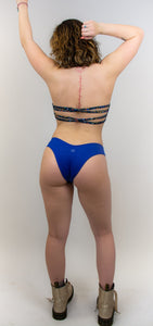 "This photo shows a model wearing the same pair of cheeky swimwear bottoms , this time in the color deep blue. There is a small ""hilo"" logo centered in the back of the bottoms. The models back is facing us."