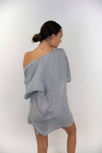 This photo shows a model whose back is facing us. This photo shows the vertical black and white stripes on the fabric. The kimono is boxy and reaches just below the hips.