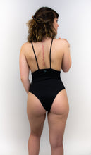 Load image into Gallery viewer, This photo is a model wearing a one piece swimsuit that is completely black. Her back is facing us. The model is facing us and there are skinny straps going horizontally down the sides of the suit.