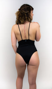 This photo is a model wearing a one piece swimsuit that is completely black. Her back is facing us. The model is facing us and there are skinny straps going horizontally down the sides of the suit.