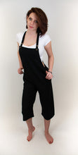 Load image into Gallery viewer, A girl with her hands on her hips is wearing a set of overalls in the a black color. The overalls' pant legs hit her mid calf and she is wearing a white shirt underneath the overalls. The overalls have two straps that can be adjusted with the two buttons on each strap. The girl wearing the overalls has dark short red hair and has blue eyes, her skin is fair and she has a smirk on her face.